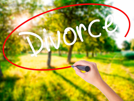 ex wife: Woman Hand Writing Divorce  on blank transparent board with a marker isolated over green field background. Business concept. Stock Photo