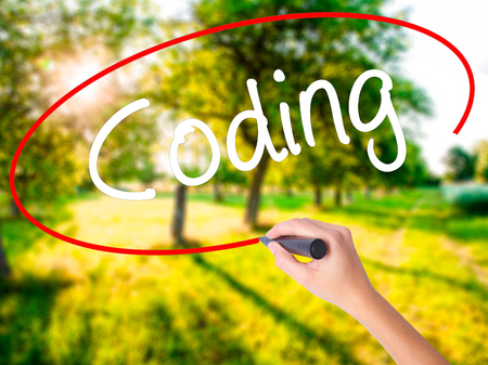 Woman Hand Writing Coding on blank transparent board with a marker isolated over green field background. Stock Photo