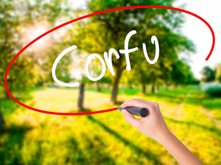 Woman Hand Writing Corfu on blank transparent board with a marker isolated over green field background. Business concept. Stock Photo Stock Photo