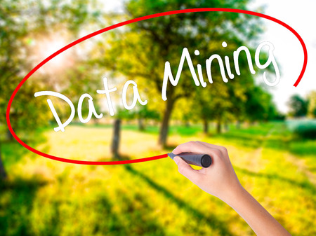Woman Hand Writing  Data Mining on blank transparent board with a marker isolated over green field background. Stock Photo
