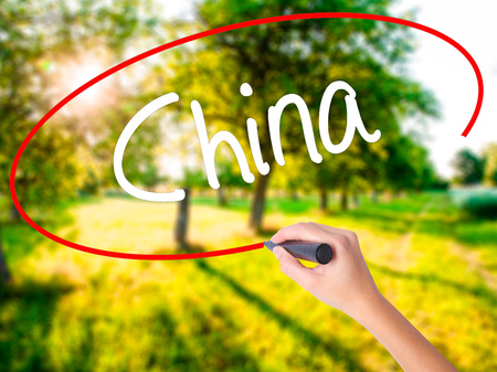 Woman Hand Writing China on blank transparent board with a marker isolated over green field background. Stock Photo