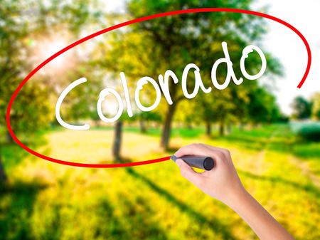 Woman Hand Writing Colorado  on blank transparent board with a marker isolated over green field background. Business concept. Stock Photo