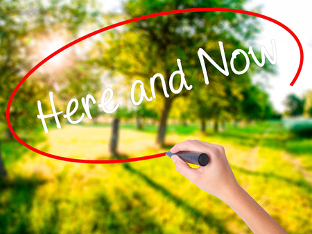 Woman Hand Writing Here and Now on blank transparent board with a marker isolated over green field background. Stock Photo