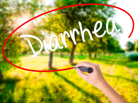 Woman Hand Writing  Diarrhea  on blank transparent board with a marker isolated over green field background. Stock Photo