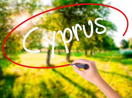 Woman Hand Writing Cyprus on blank transparent board with a marker isolated over green field background. Stock Photo Stock Photo