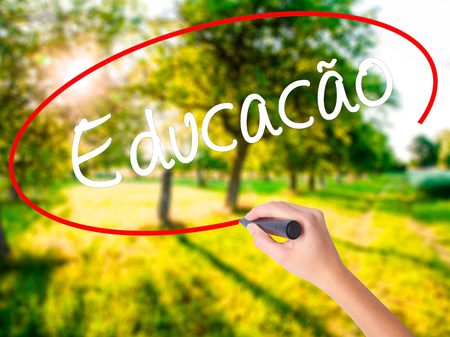 Woman Hand Writing Education (Educacao in Portuguese) on blank transparent board with a marker isolated over green field background. Stock Photo