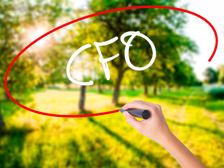 Woman Hand Writing CFO (Chief Financial Officer) on blank transparent board with a marker isolated over green field background. Stock Photo