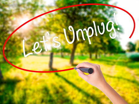 Woman Hand Writing Lets Unplug! on blank transparent board with a marker isolated over green field background. Business concept. Stock Photo