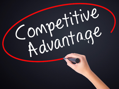 correlate: Woman Hand Writing Competitive Advantage on blank transparent board with a marker isolated over black background. Business concept. Stock Photo