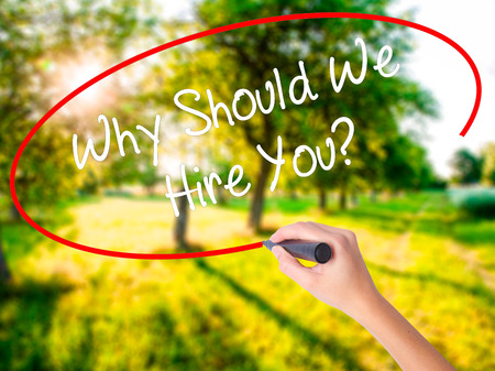 Woman Hand Writing Why Should We Hire You? on blank transparent board with a marker isolated over green field background. Stock Photo