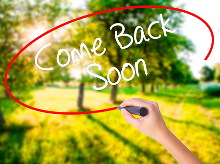 Woman Hand Writing Come Back Soon on blank transparent board with a marker isolated over green field background. Stock Photo