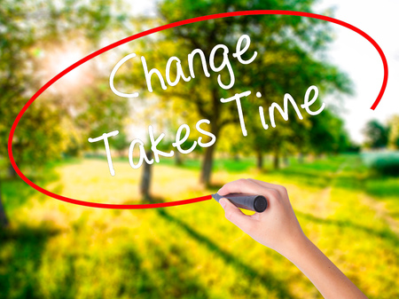 Woman Hand Writing Change Takes Time on blank transparent board with a marker isolated over green field background. Stock Photo