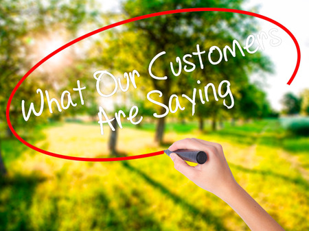 testimonials: Woman Hand Writing What Our Customers Are Saying on blank transparent board with a marker isolated over green field background. Business concept. Stock Photo