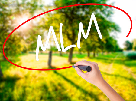 Woman Hand Writing  MLM (Multi-Level Marketing) on blank transparent board with a marker isolated over green field background. Stock Photo Stock Photo