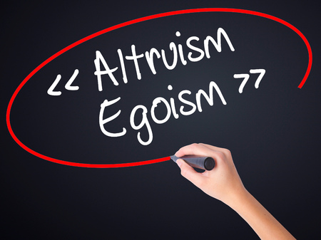 altruismo: Woman Hand Writing Altruism - Egoism on blank transparent board with a marker isolated over black background. Stock Photo Foto de archivo