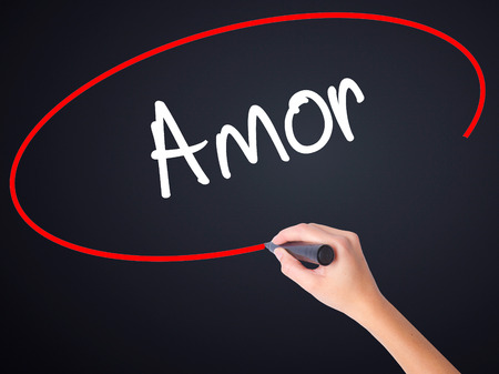 Woman Hand Writing Amor ( Love in Portuguese)on blank transparent board with a marker isolated over black background. Business concept. Stock Photo
