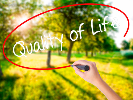 Woman Hand Writing Quality of Life on blank transparent board with a marker isolated over green field background. Stock Photo