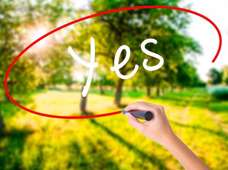 opinions: Woman Hand Writing Yes on blank transparent board with a marker isolated over green field background. Business concept. Stock Photo