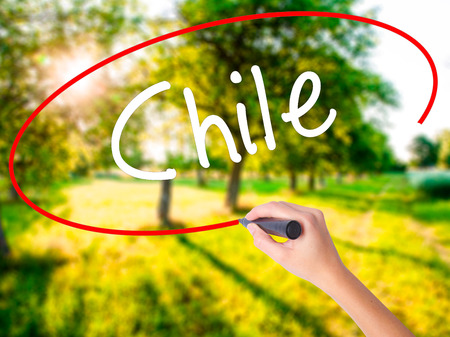 Woman Hand Writing Chile  on blank transparent board with a marker isolated over green field background. Business concept. Stock Photo