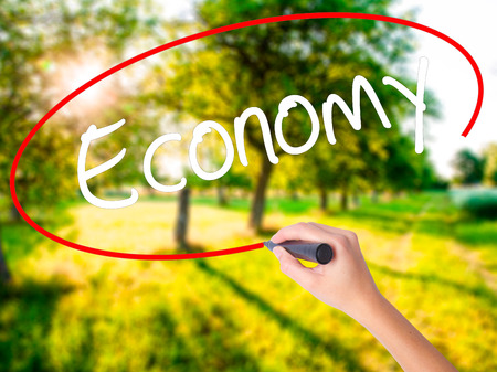 Woman Hand Writing Economy on blank transparent board with a marker isolated over green field background. Stock Photo