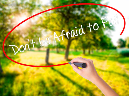 Woman Hand Writing Dont be Afraid to Fail on blank transparent board with a marker isolated over green field background. Business concept. Stock Photo