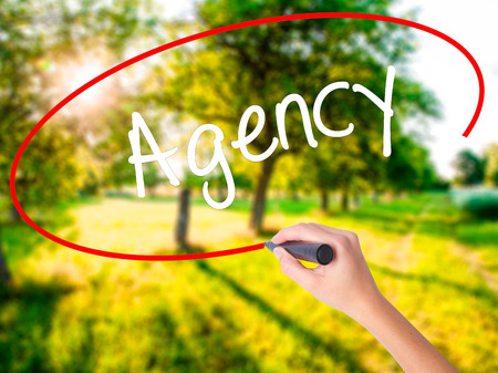 Woman Hand Writing Agency on blank transparent board with a marker isolated over green field background. Business concept. Stock Photo