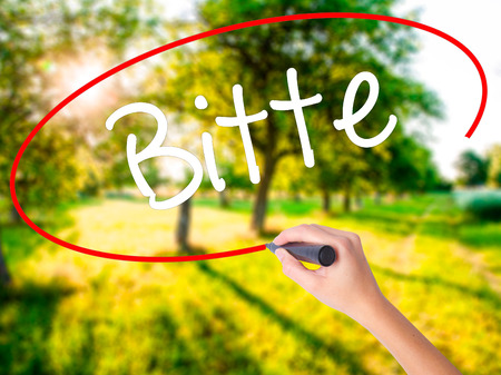 Woman Hand Writing Bitte (Please in German) on blank transparent board with a marker isolated over green field background. Stock Photo Stock Photo