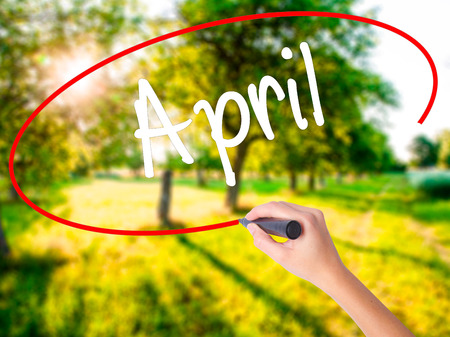 Woman Hand Writing  April  on blank transparent board with a marker isolated over green field background. Business concept. Stock Photo Stock Photo