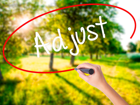 Woman Hand Writing Adjust on blank transparent board with a marker isolated over green field background. Stock Photo