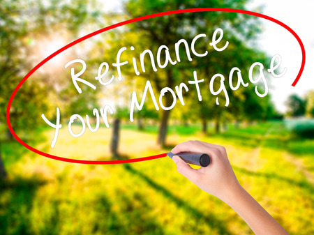 Woman Hand Writing Refinance Your Mortgage on blank transparent board with a marker isolated over green field background. Business concept. Stock Photo