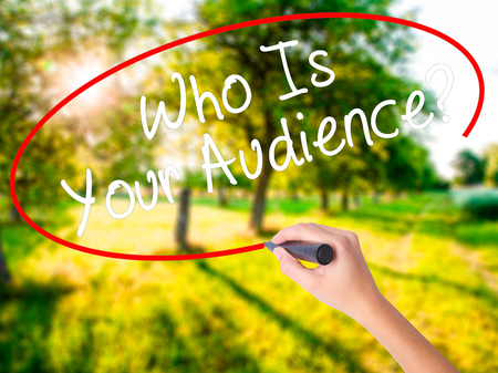 Woman Hand Writing Who Is Your Audience? on blank transparent board with a marker isolated over green field background. Business concept. Stock Photo