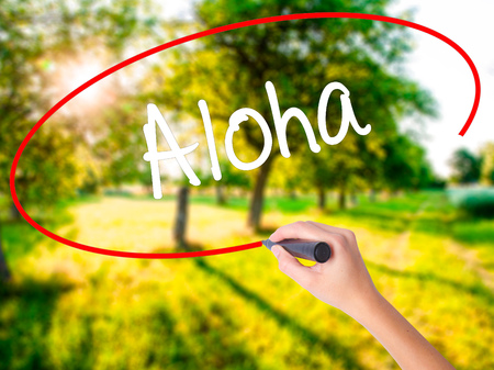 Woman Hand Writing Aloha  on blank transparent board with a marker isolated over green field background. Business concept. Stock Photo