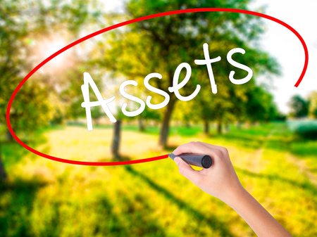 Woman Hand Writing Assets on blank transparent board with a marker isolated over green field background. Business concept. Stock Photo