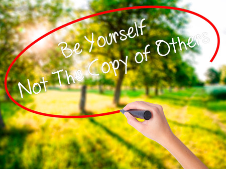 Woman Hand Writing Be Yourself Not The Copy of Others on blank transparent board with a marker isolated over green field background. Business concept. Stock Photo  Stock Photo