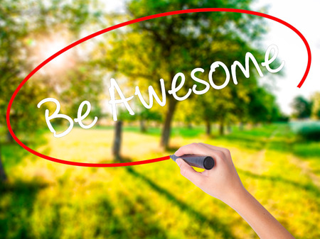 feeling happy: Woman Hand Writing Be Awesome on blank transparent board with a marker isolated over green field background. Business concept. Stock Photo
