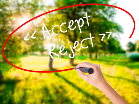 approvement: Woman Hand Writing Accept - Reject  on blank transparent board with a marker isolated over green field background. Stock Photo Stock Photo