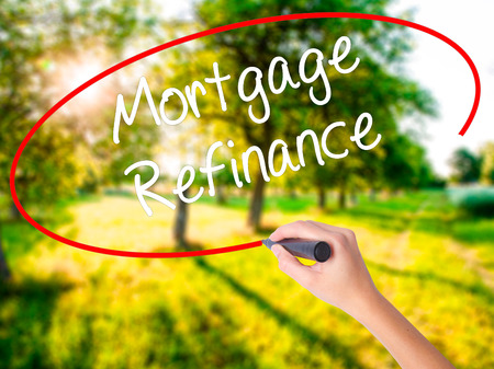 Woman Hand Writing Mortgage Refinance on blank transparent board with a marker isolated over green field background. Business concept. Stock Photo