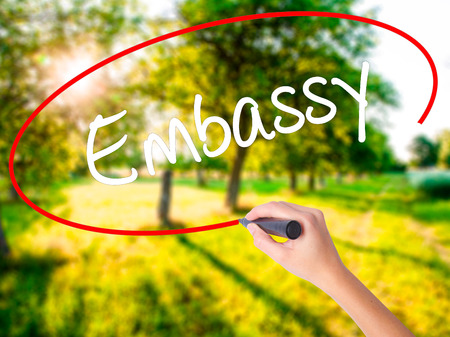 Woman Hand Writing Embassy on blank transparent board with a marker isolated over green field background. Business concept. Stock Photo