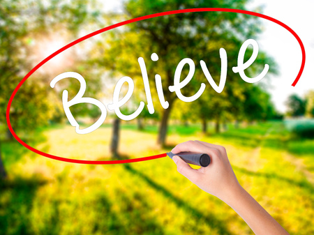 Woman Hand Writing Believe on blank transparent board with a marker isolated over green field background. Business concept. Stock Photo