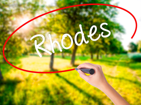 tsambika: Woman Hand Writing Rhodes on blank transparent board with a marker isolated over green field background. Business concept. Stock Photo