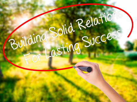 lasting: Woman Hand Writing Building Solid Relations For Lasting Success on blank transparent board with a marker isolated over green field background. Business concept. Stock Photo Stock Photo