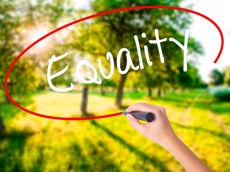 Woman Hand Writing Equality  on blank transparent board with a marker isolated over green field background. Business concept. Stock Photo Stock Photo