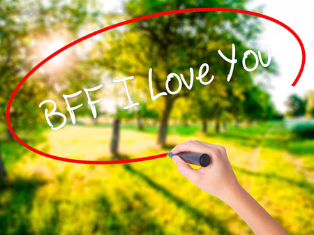 in loving memory: Woman Hand Writing BFF I Love You on blank transparent board with a marker isolated over green field background. Business concept. Stock Photo