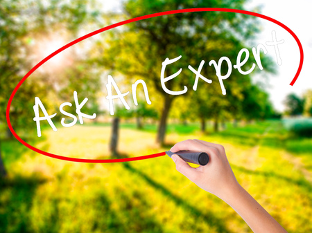 opinions: Woman Hand Writing Ask An Expert on blank transparent board with a marker isolated over green field background. Business concept. Stock Photo