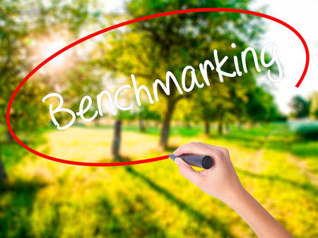 specific: Woman Hand Writing Benchmarking  on blank transparent board with a marker isolated over green field background. Business concept. Stock Photo
