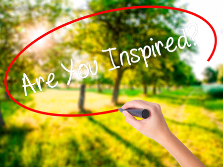 Woman Hand Writing Are You Inspired? on blank transparent board with a marker isolated over green field background. Stock Photo