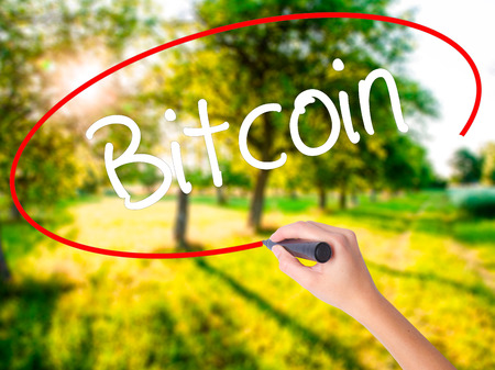 bitcoin network: Woman Hand Writing Bitcoin on blank transparent board with a marker isolated over green field background. Stock Photo