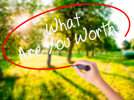 Woman Hand Writing What Are You Worth? on blank transparent board with a marker isolated over green field background. Business concept. Stock Photo