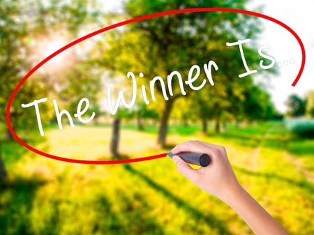Woman Hand Writing The Winner Is... on blank transparent board with a marker isolated over green field background. Business concept. Stock Photo