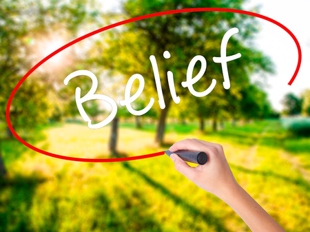 Woman Hand Writing Belief on blank transparent board with a marker isolated over green field background. Business concept. Stock Photo